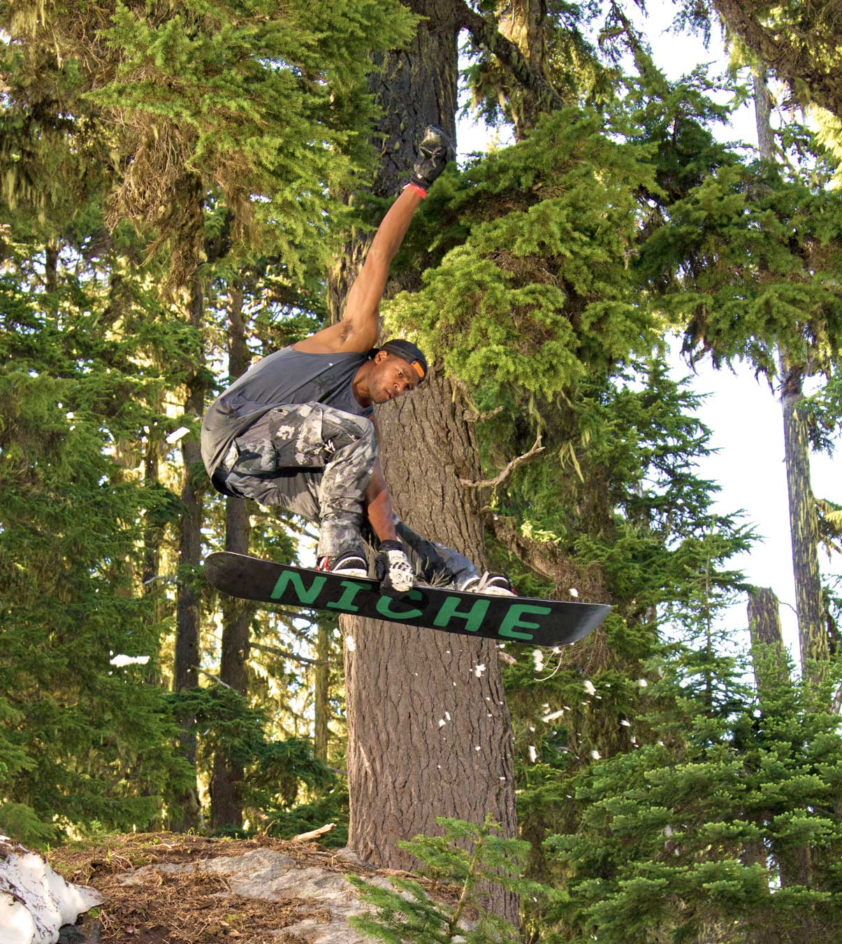 Snowboarder catching air in forest