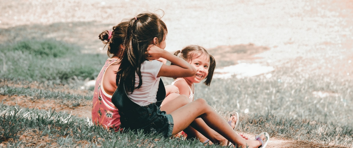 Earth Day is a good time to begin encouraging kids to get curious about the great outdoors. Three children seated in grass.