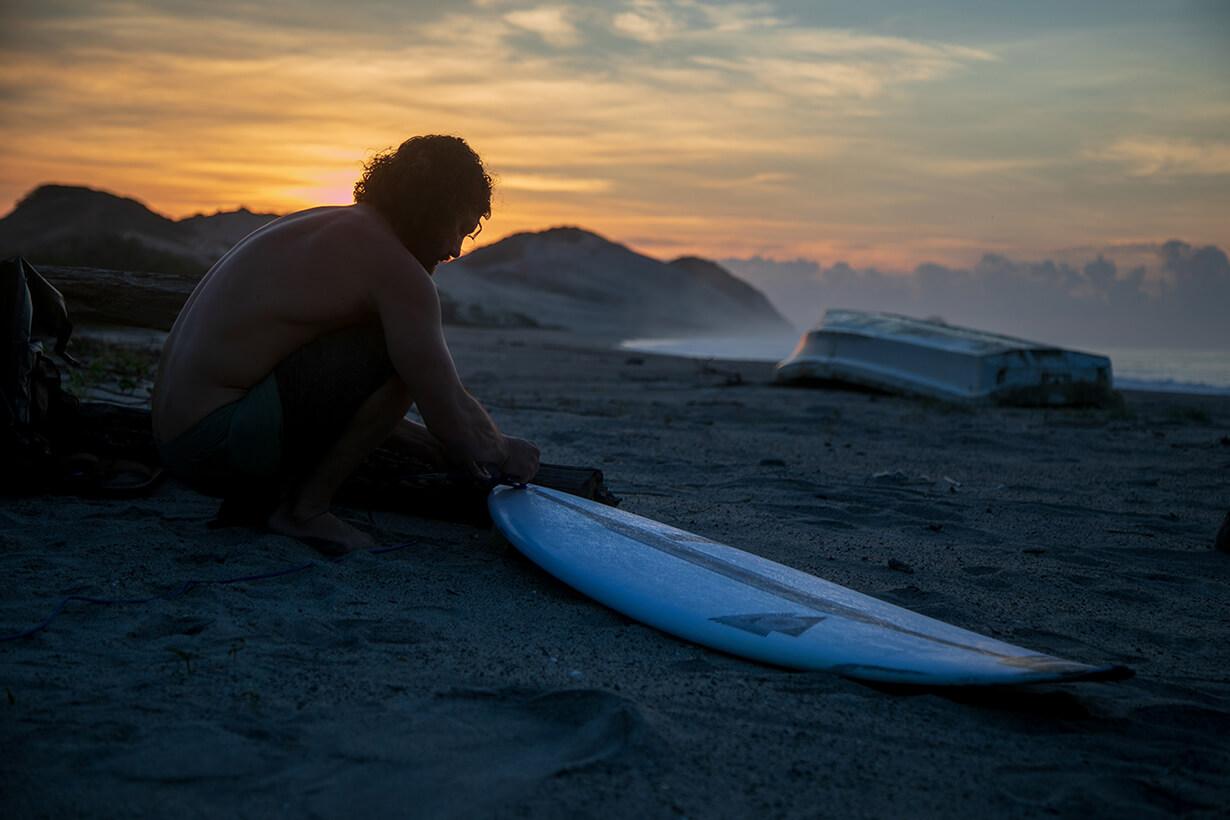 Surfer preparing surfboard