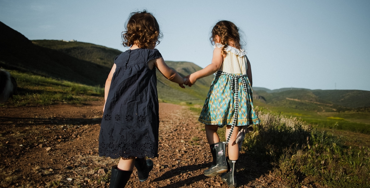 Teach children the importance of treading lightly on the Earth by always setting a great example of how it's done. Two children walking outdoors and holding hands.