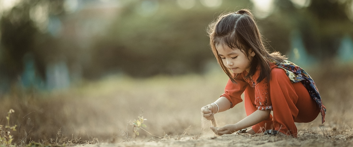Encourage kids to closely examine Mother Earth to engage their tactile senses and natural curiosity. A young child sifts through the dirt.