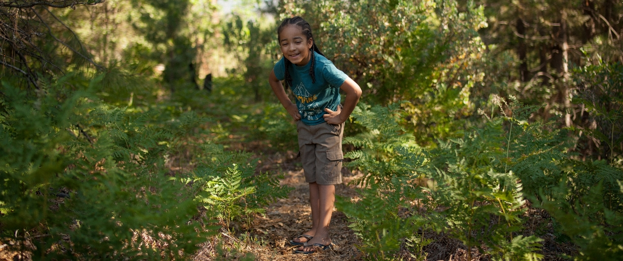As you and your child happily explore the woods this Earth Day, tune into the beautiful sounds that nature has to offer. Child smiling while exploring the woods.