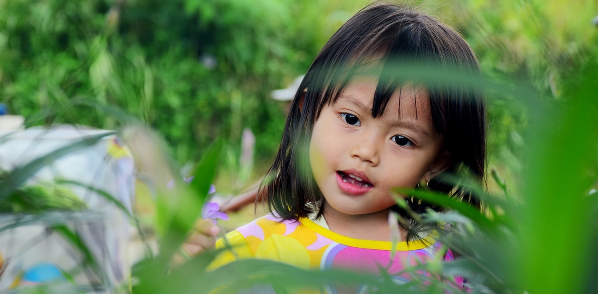 With your help, nature can teach a child the subtleties of colors. Small child admiring a purple flower.